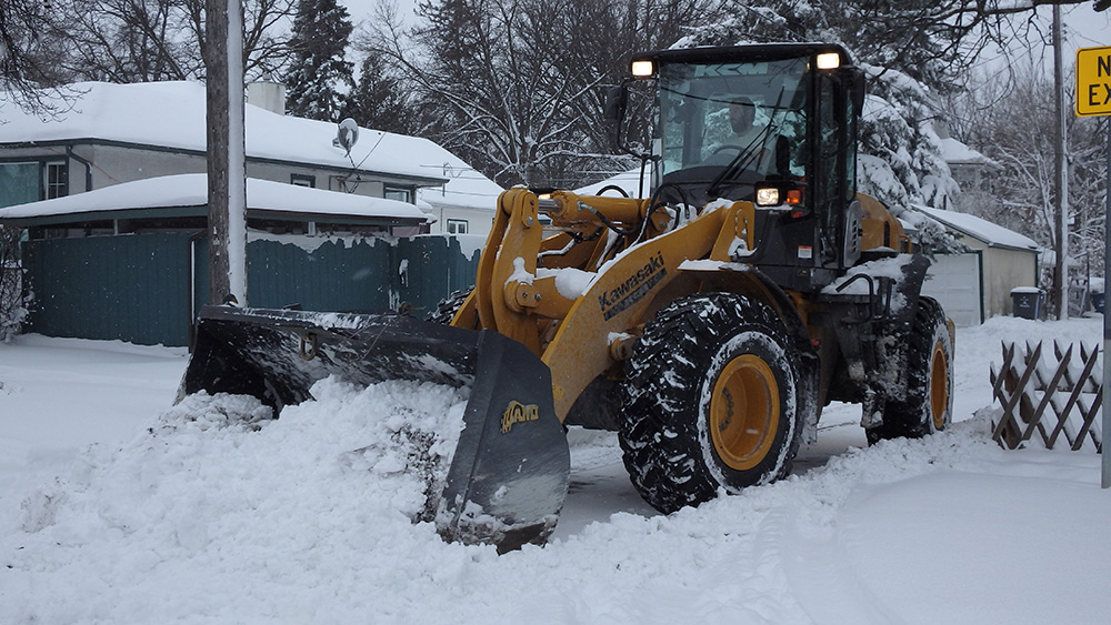 Front end loaders working to clear back lanes across Winnipeg