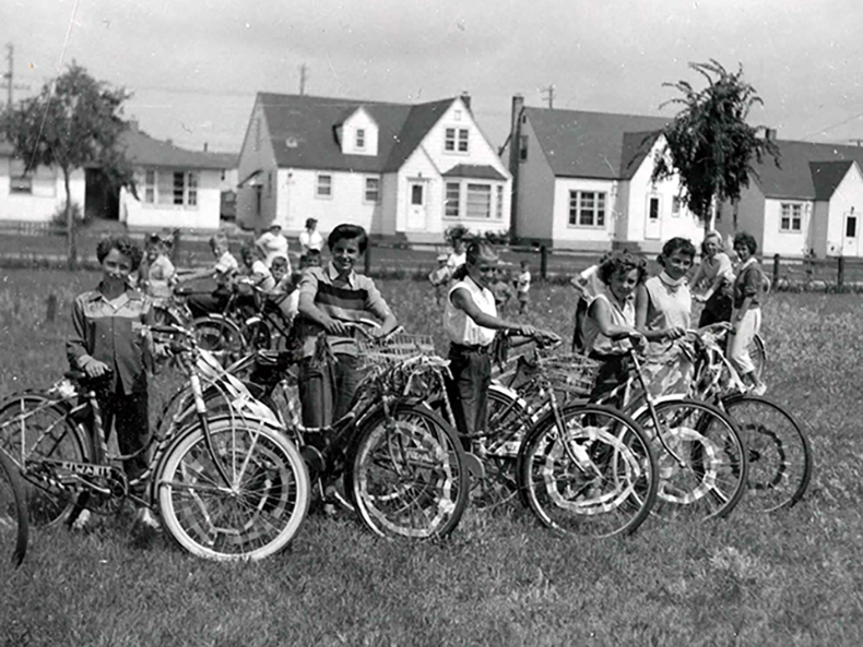 Group shot of kids posing with their bicycles, October 1955.