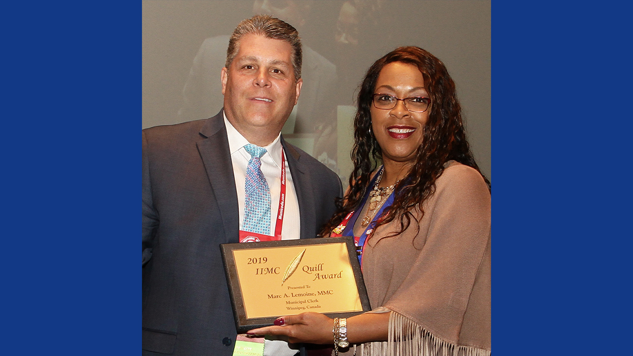 Marc Lemoine is presented the Quill Award by Stephanie Kelly, City Clerk of Charlotte, North Carolina.