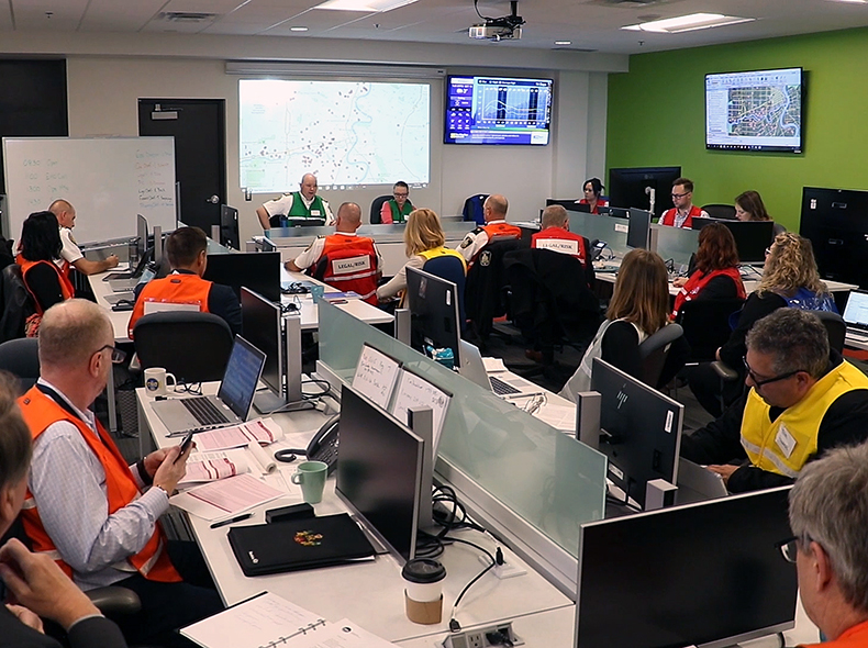 People sitting at desks in the Emergency Operations Centre (EOC)