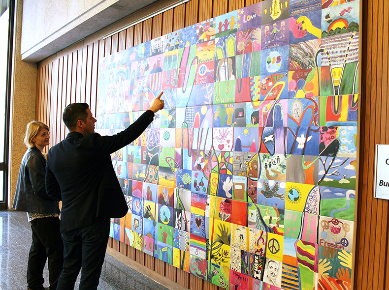 Mayor Brian Bowman is shown the 'Everybody has the Right' mural by Emma Prescott, HSC Winnipeg Archivist.